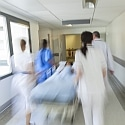 A motion blurred photograph of a child patient on stretcher or gurney being pushed at speed through a hospital corridor by doctors & nurses to an accident and emergency room